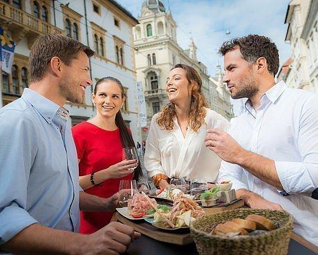 Zwei Pärchen speisen an einer Bar in der Fußgängerzone von Graz