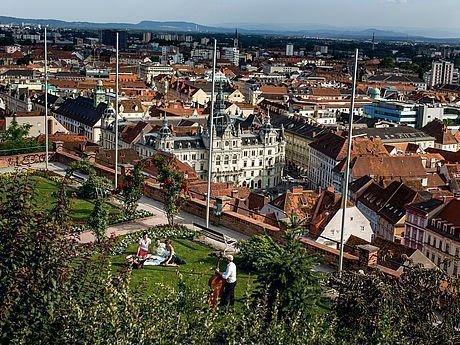 Junge Menschen beim Picknick am Schlossberg in Graz mit Blick auf die Stadt
