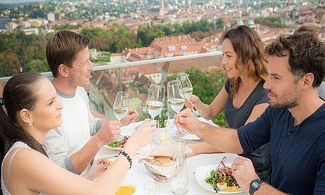 Zwei Pärchen essen über den Dächern der Stadt Graz im Sommer