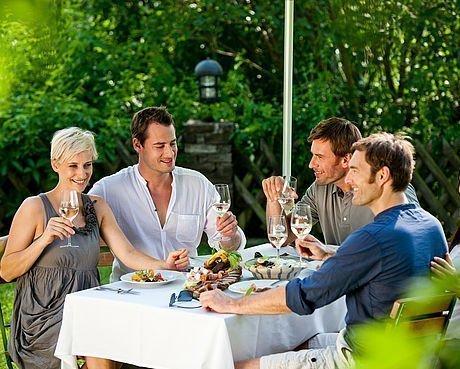 Freunde genießen im Sommer Wein im Buschenschank in Graz