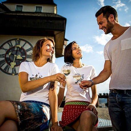 Menschen trinken Wein und genießen das Grazer Stadtleben vor dem Uhrturm